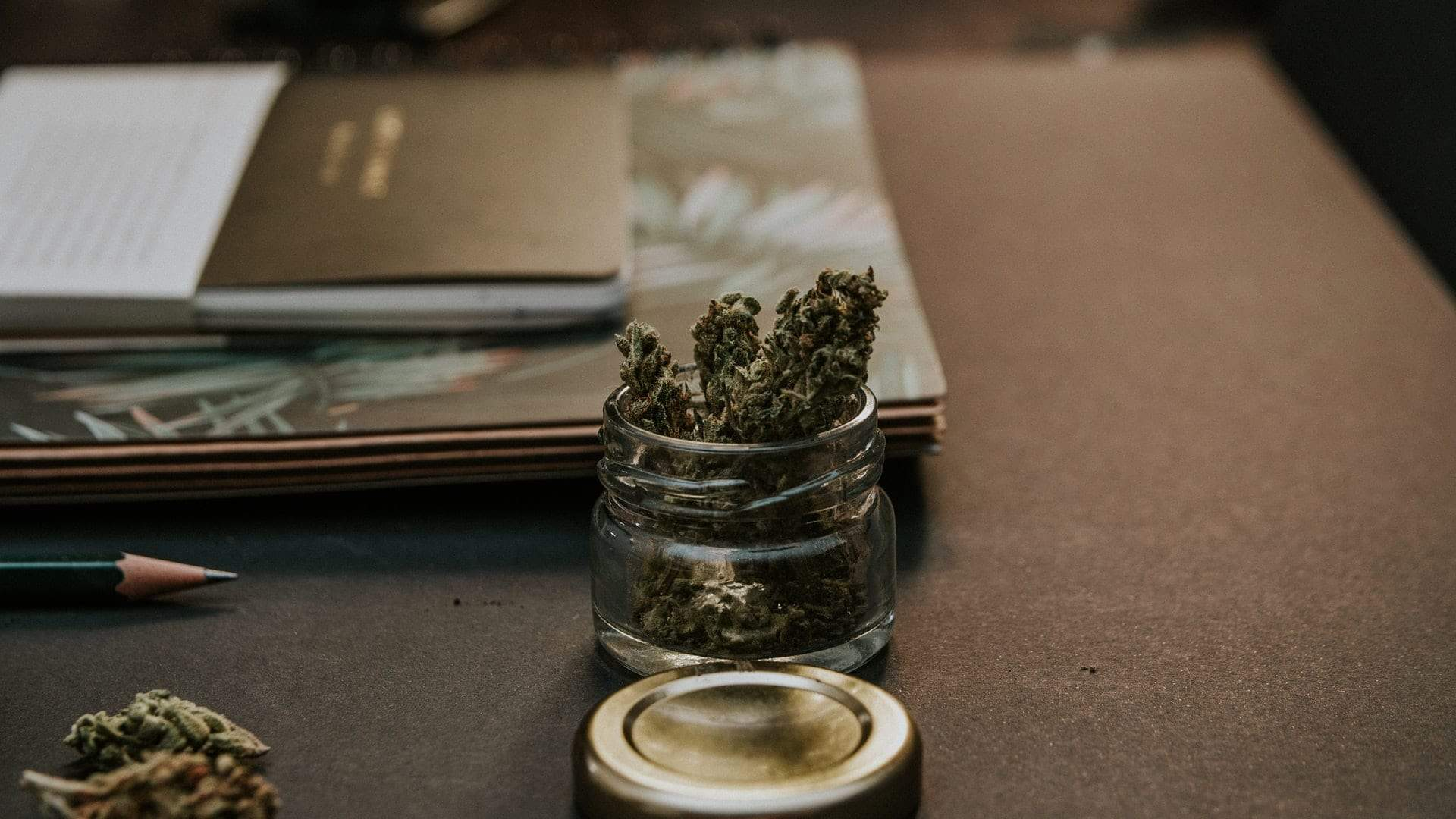 Cannabis buds in a jar on a desk