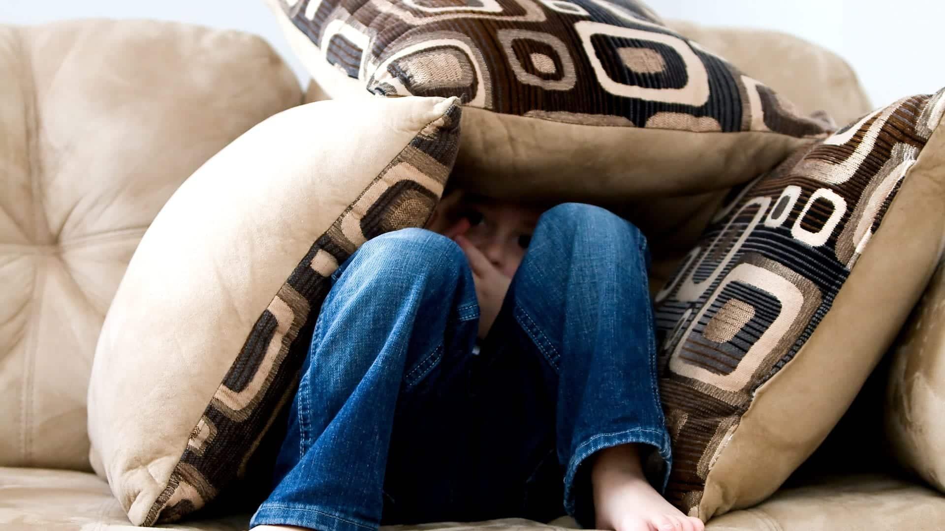 Child hiding behind cushions