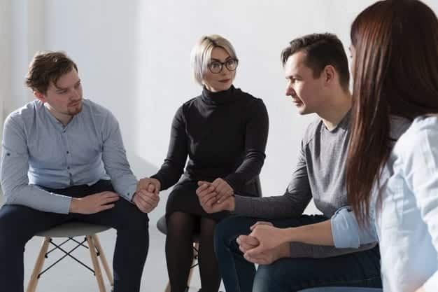 Female doctor counsellor at group therapy holding hands