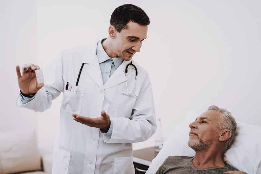 Doctor talking to patient in bed