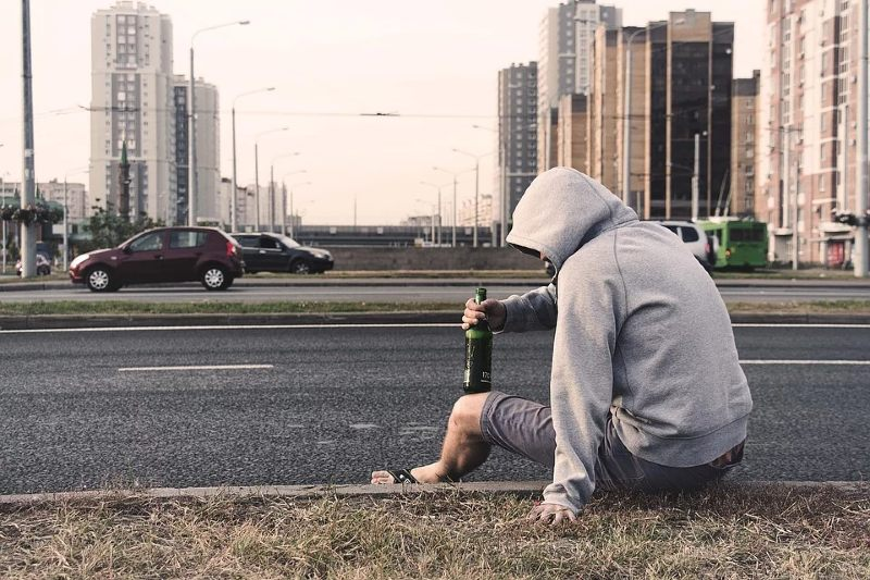 Man sitting by the side of the road drinking alcohol from a bottle